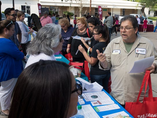 People talk to vendors during the opening of the Healthy