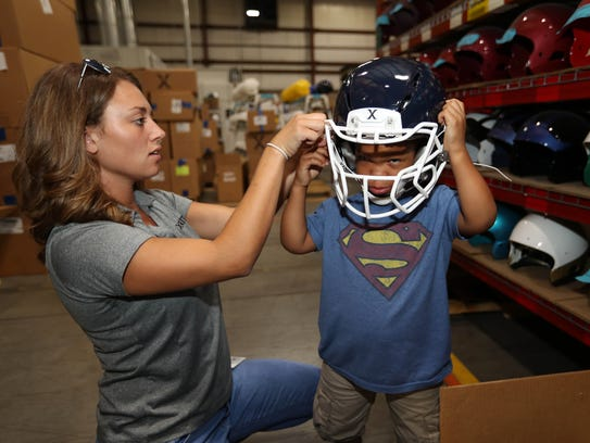 Trey Banks gets a hand with his football helmet from