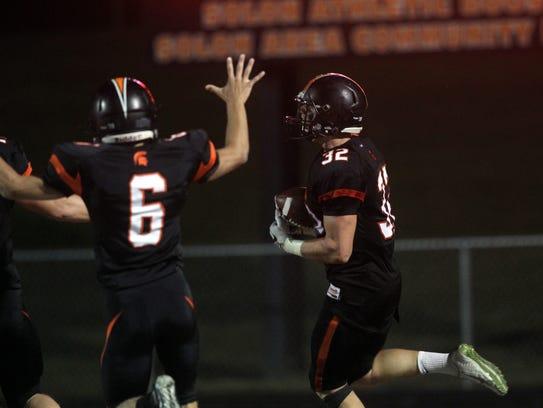 Solon's Adam Bock takes his interception in for a touchdown