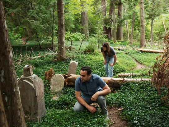 Dan Trepal, senior research associate with the Keweenaw Time Traveler project, and Sarah Fayen Scarlett, assistant professor of history at Michigan Technological University in Houghton, look over gravestones in the overgrown Cliff Cemetery in Michigan's U.P.