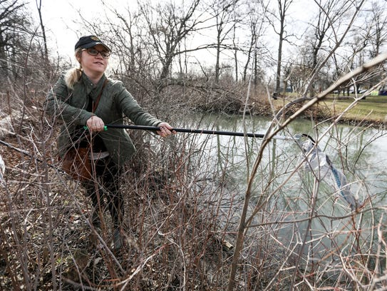 Stefani Flack, 29, of Ferndale cleans up trash from