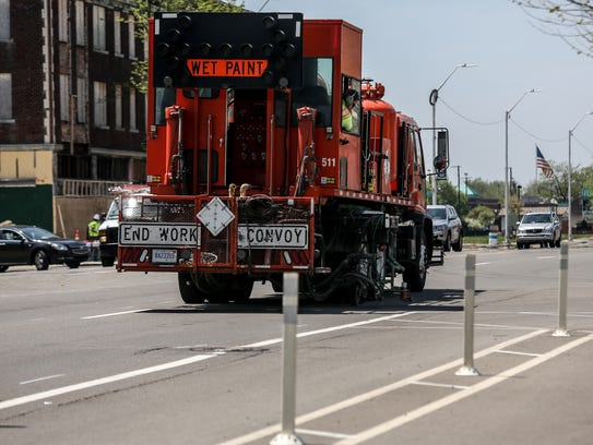 Workers paint bike lanes along East Jefferson Avenue in Detroit near the border with Grosse Pointe on Wednesday, May 16, 2018