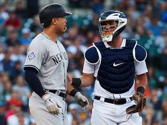 James McCann stands between Giancarlo Stanton and Tigers pitcher Mike Fiers (not pictured), after Stanton was hit by a pitch in the third inning.