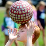 Hayes Thomas, 9, balances a kick-ball on his head during the 2014 University of Southern Mississippi's Quidd-Lit Summer Camp at the university's Pride Field.