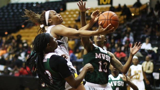 Grambling guard Monisha Neal shoots to score as Mississippi Valley State University forward Kenya Hailey (right) and forward Jazmine Torian (left) attempt to block her during the SWAC quarterfinals at Fredrick C. Hobdy Arena on Tuesday, March 7, 2017. Neal made the basket and the Lady Tigers went on to defeat the Delta Devilettes 71-61.