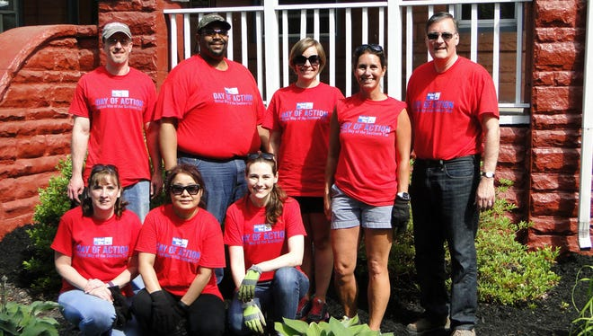 Members of the Corning Inc. corporate committee helped spread mulch at two Glove House group homes in Elmira. Pictured, standing, from left, Joe Staats, Ronnie Harper, Julie Whitehouse, Kristine Dale and Gary Calabrese; kneeling, from left, Terri Speciale, Phila Tarlton and Katie Greene.