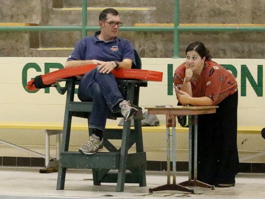 Notre Dame head coach Julianne Dunn and assistant Francis Craig talk as their swimmers complete laps during a recent practice at Elmira High School.
