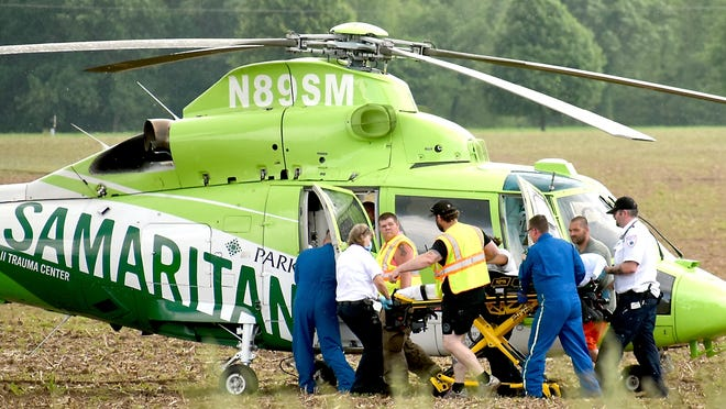 Crew members of LifeCAre and Samaritan load a mother and her 3-year-old son for a flight to Parkview Hospital in Fort. Wayne, Ind., after both were injured Friday in a lawn mower accident in Sherwood Township.