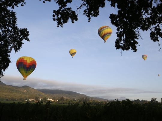Hot air balloons rise just after dawn over vineyards in Yountville, California.