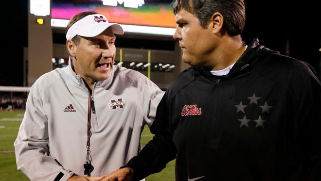 Mississippi State head coach Dan Mullen, left, and Ole Miss head coach Matt Luke wish each other good luck prior to the start of the Egg Bowl Thursday in Starkville.