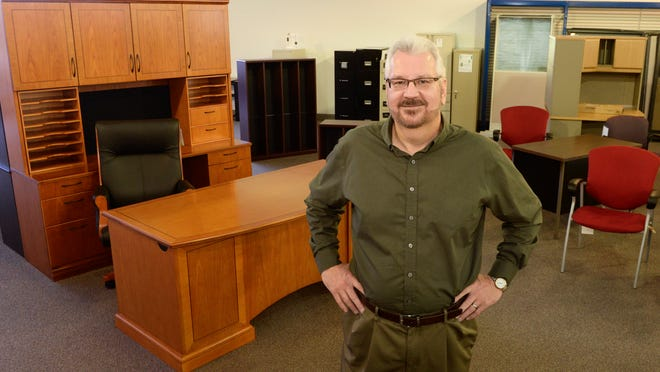 Tom Kriedeman, owner and president of Badger Office City in Manitowoc, in the showroom with a contemporary cherry wood executive office furniture.