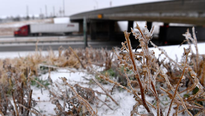 Frozen weeds and grass line Interstate 20 at the Westlake Road bridge as an 18-wheeler heads east Wednesday Feb. 21, 2018.  The day's ice storm slowed the Big Country to a halt, closing schools and businesses across the region as sleet and freezing rain fell off an on most of the day.