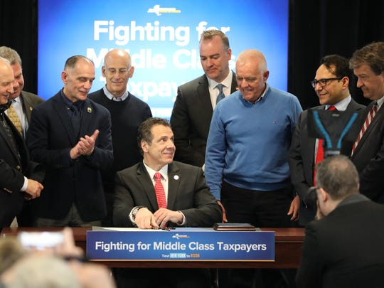 New York State Gov. Andrew Cuomo signs a New York State