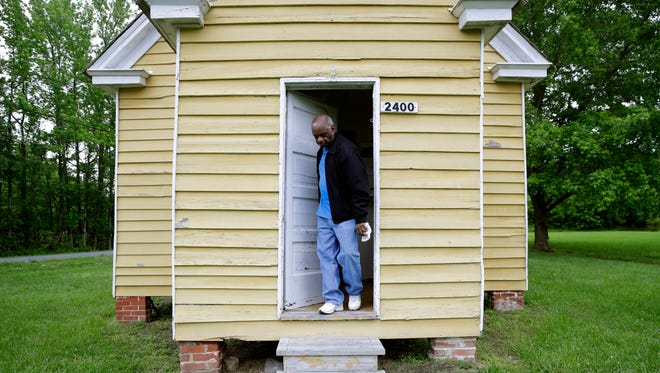 In this May 12, 2017 photo, Herschel Johnson steps out of a former one-room schoolhouse for black students known as the Stanley Institute in Cambridge, Md.