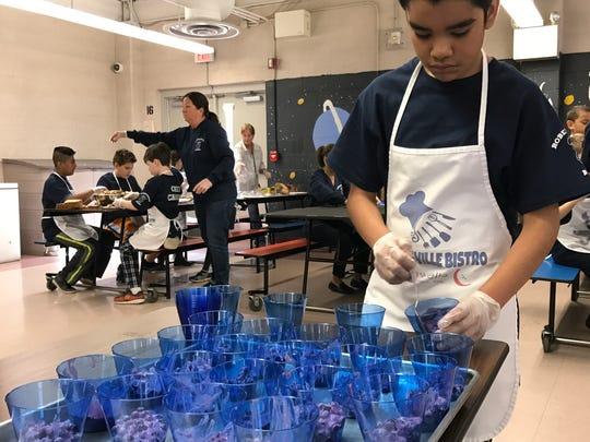 Fifth-grader Miguel Romero, 11, is preparing to serve the yogurt dish as part of the bistro program at Robertsville Elementary School in Marlboro.