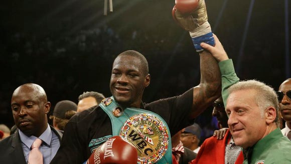 Deontay Wilder holds up his arm after he defeates Eric