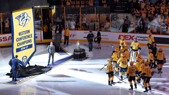 Former captain Mike Fisher and current captain Roman Josi unveil the Western Conference Final banner before the home opener at Bridgestone Arena in Nashville, Tenn., Tuesday, Oct. 10, 2017.
