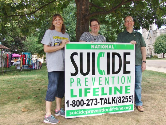 From left, Leane Rohr, Jessica Paynter and Tom Wilson pose for a photo Saturday at the suicide prevention awareness event held at the court square in Coshocton.