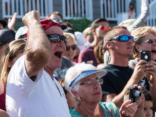 Crowd members cheer as the largest white marlin is