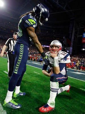 Seattle Seahawks cornerback Richard Sherman (left) shakes hands with New England Patriots quarterback Tom Brady (12) after Super Bowl XLIX at University of Phoenix Stadium.
