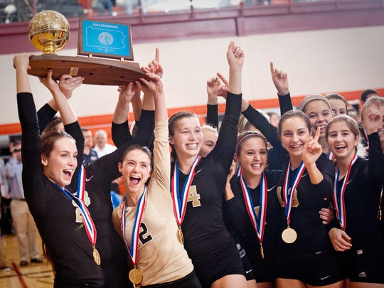 Delone Catholic volleyball players Cambria Wierman, Mary Gingrow and Hannah Lawrence hold up the PIAA Class AA state championship trophy as teammates celebrate around them after the Squirettes defeated Fort LeBoeuf at Central York on Saturday, Nov. 16, 2013