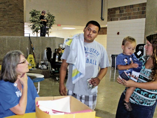 Kay McClune, a registered nurse, gives Fabian Pena and Katalyna McCall information on Pediatrics of Alamogordo during the first annual resource expo hosted by GRADS.