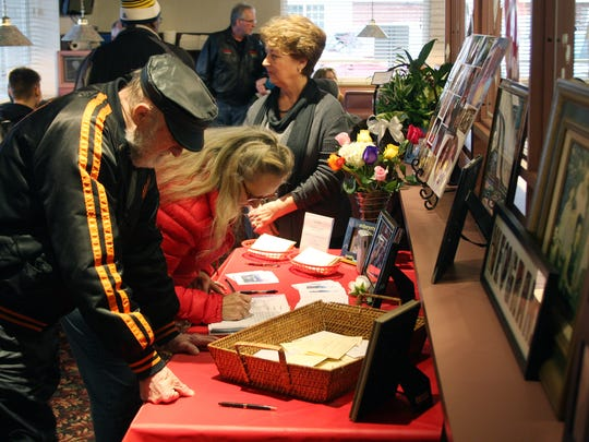 Cards and a guest book were set out by the photographs of Joan Kain with her loving family during the memorial service at The Pancake House Saturday afternoon