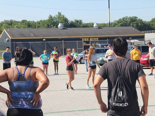 Newark High School marching band members organize their own practice in the school's parking lot on Wednesday, Aug. 9, 2017.