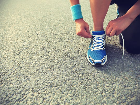 Runner tying shoelaces on city road.
