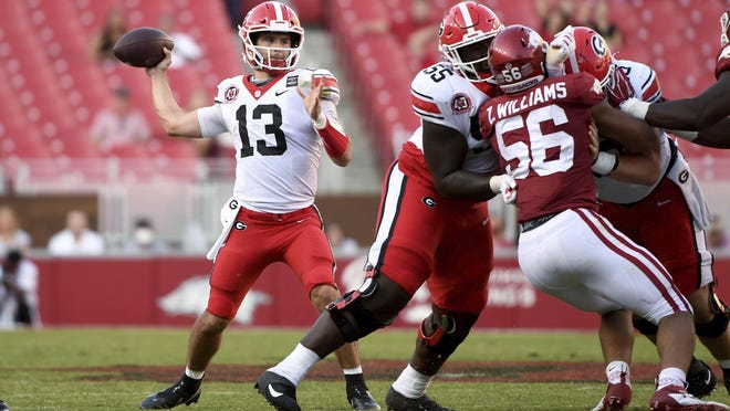 Georgia quarterback Stetson Bennett (13) throws a pass against Arkansas while offensive lineman Trey Hill (55) blocks during the second half of an NCAA college football game in Fayetteville, Ark. Saturday, Sept. 26, 2020.