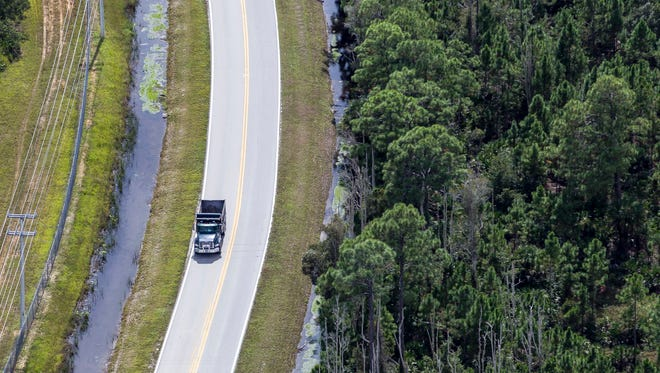 A dump truck drives along rural Corkscrew Road in Lee County on Friday, Oct. 25, 2013.