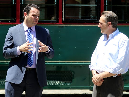 Mayor Andre Sayegh and David Garsia, right. At this July press conference, Garsia had said the trolleys would begin running by the end of July. He recently changed that to mid- or late October.