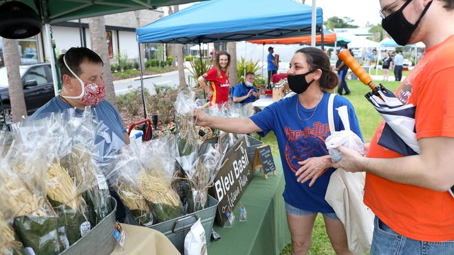 Tracie Faria, center, and her partner James Nall get a bag of artisan pasta from Michel Martin, left, at his Bleu Basil booth during the Farmers Market at Celebration Pointe in Gainesville on Wednesday.