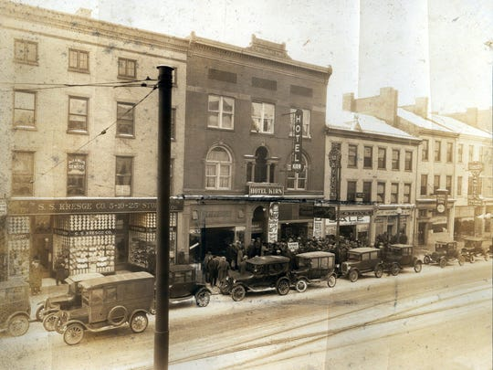 """A new Hotel Kirn opened on the south side of Main Street in 1895. As the photo shows the entrance to the hotel was in the center of two stores on the ground level. The Kirn Brothers shoe store was on the east side and Joe Mattox's clothing store was on the west. The Mattox sign shown on a pole in front of the store is reported to have been the first electric sign with a """"moving attraction"""" on Main Street. Photo was taken in January 1926."""