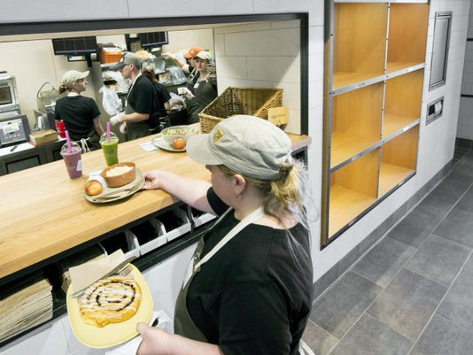 Tia Keller, of York, handles a practice order at Panera Bread on Wednesday. The cubbyholes to the right will be used for pickup orders. The restaurant had its grand opening Thursday.