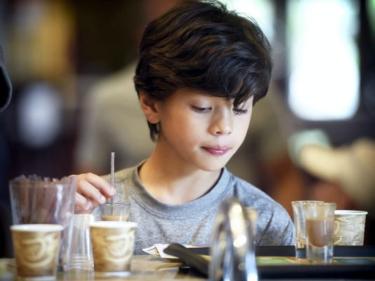 Ten-year-old Lucas Gutierrez of Sugarland, Texas, samples chocolates at The Hershey Story Wednesday afternoon. The Hershey Story is now offering a chocolate Tastings experience. The intimate bar offers melted chocolate drink samples from the osland of Java, Tanzania, Ghana, Venezuela, Mexico — and Hershey. Each sample, except the Hershey Milk Chocolate itself, originates from a single-origin bean.