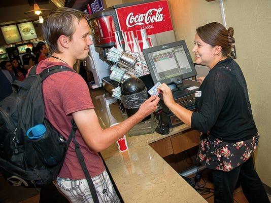 Jett Loe--Sun-News   NMSU Freshman Josh Diven hands Lynda Garcia a payment card for lunch at Corbett Center Student Union.