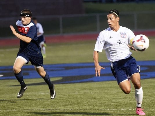 Erik Espinoza (7) of Chambersburg speeds past the defense and chases down a pass from Eric Dixon before scoring the game's first goal on Thursday in the Trojans' 3-1 win. Red Land's Josh Craley (12) is in pursuit.