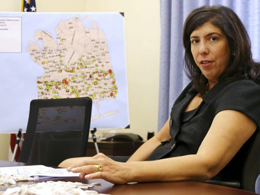 FILE- In this Sept. 9, 2015 file photo, acting Nassau County District Attorney Madeline Singas is seated at her desk in Mineola, N.Y. Singas relaxed the restriction the District Attorney's Office had against prosecutors owning firearms but still prohibits them from carrying guns at work. (AP Photo/Mike Balsamo, File)