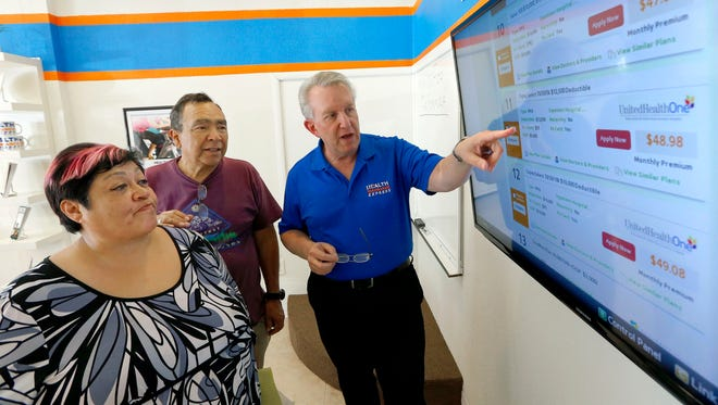 Alan Leafman, right, president of Health Insurance Express, Inc., discusses insurance plans on Oct. 1 to Raquel Bernal, left, and her husband, John Bernal, in Mesa, Ariz.