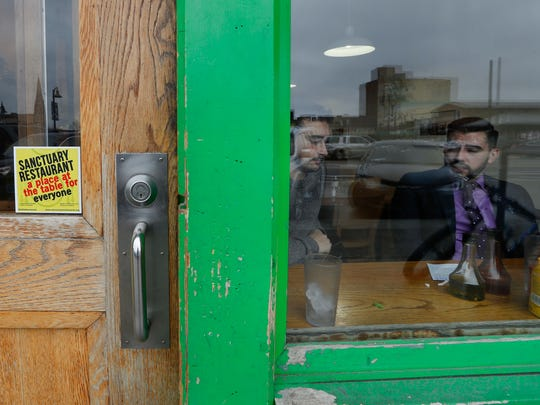 """In this Wednesday, Jan. 18, 2017 photo, a sanctuary restaurant sign is shown on the door of the Russell Street Deli in Detroit. Dozens of restaurants are seeking """"sanctuary"""" status, a designation owners hope will help protect employees in an immigrant-heavy industry and tone down fiery rhetoric sparked by the presidential campaign."""