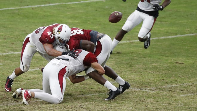 Arizona Cardinals linebacker Alani Fua pops the ball out of tight end Gerald Christian's  arms during Red and White practice at University of Phoenix Stadium in Glendale on Saturday, August, 8, 2015.