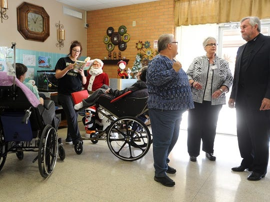 Then-state Sen. Troy Fraser (right) speaks to Center Director Linda Hinshaw (center) and Registered Nurse Kathy Brannon, left, during a tour of a residential hall at the Abilene State Supported Living Center in December 2014. Alyssa Lara (far left) reads a book to some of the residents.