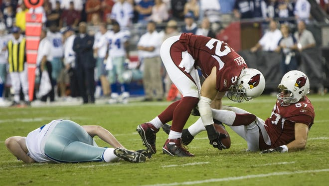 Cardinals' Monty Beisel picks up a ball for the game-winning touchdown after Sean Morey, right, blocked a punt by Cowboys' Mat McBriar in OT at University of Phoenix Stadium in Glendale October 12, 2008.