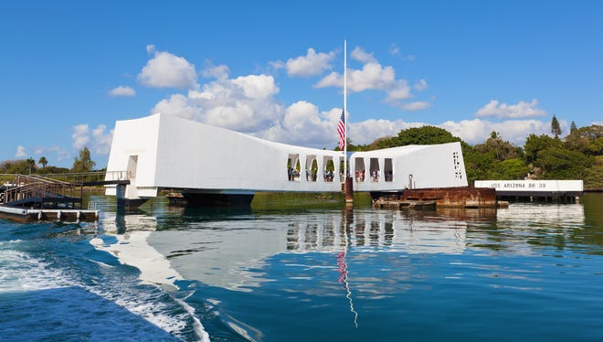 """Visit Pearl Harbor, Oahu:  Each year, nearly 2 million people visit this memorial, officially part of the World War II Valor in the Pacific National Monument. This solemn, gently sloping structure, accessible only by boat, straddles the sunken USS Arizona and memorializes those who were killed in the Pearl Harbor attacks on Dec. 7, 1941. According to Alfred Preis, the memorial's architect, """"The structure sags in the center but stands strong and vigorous at the ends, express[ing] initial defeat and ultimate victory."""" Each rising end is a testament to the optimism during times of peace. Eerily — but beautifully — the sunken ship's oil can still be seen bubbling up from the wreckage and pooling in concentric rainbows on the water's surface."""
