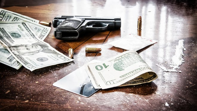 Cocaine, gun and lots of American money to represent an illegal drug transaction