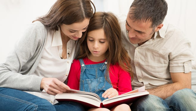 A mom and dad reading with their daughter.