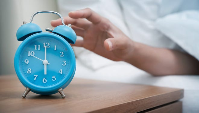 Woman hand reaching out bed for retro alarm clock. Early morning.