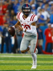 Ole Miss Rebels quarterback Jordan Ta'amu (10) runs the ball against the Kentucky Wildcats in the second half at Commonwealth Stadium. Ole Miss defeated Kentucky 37-34.