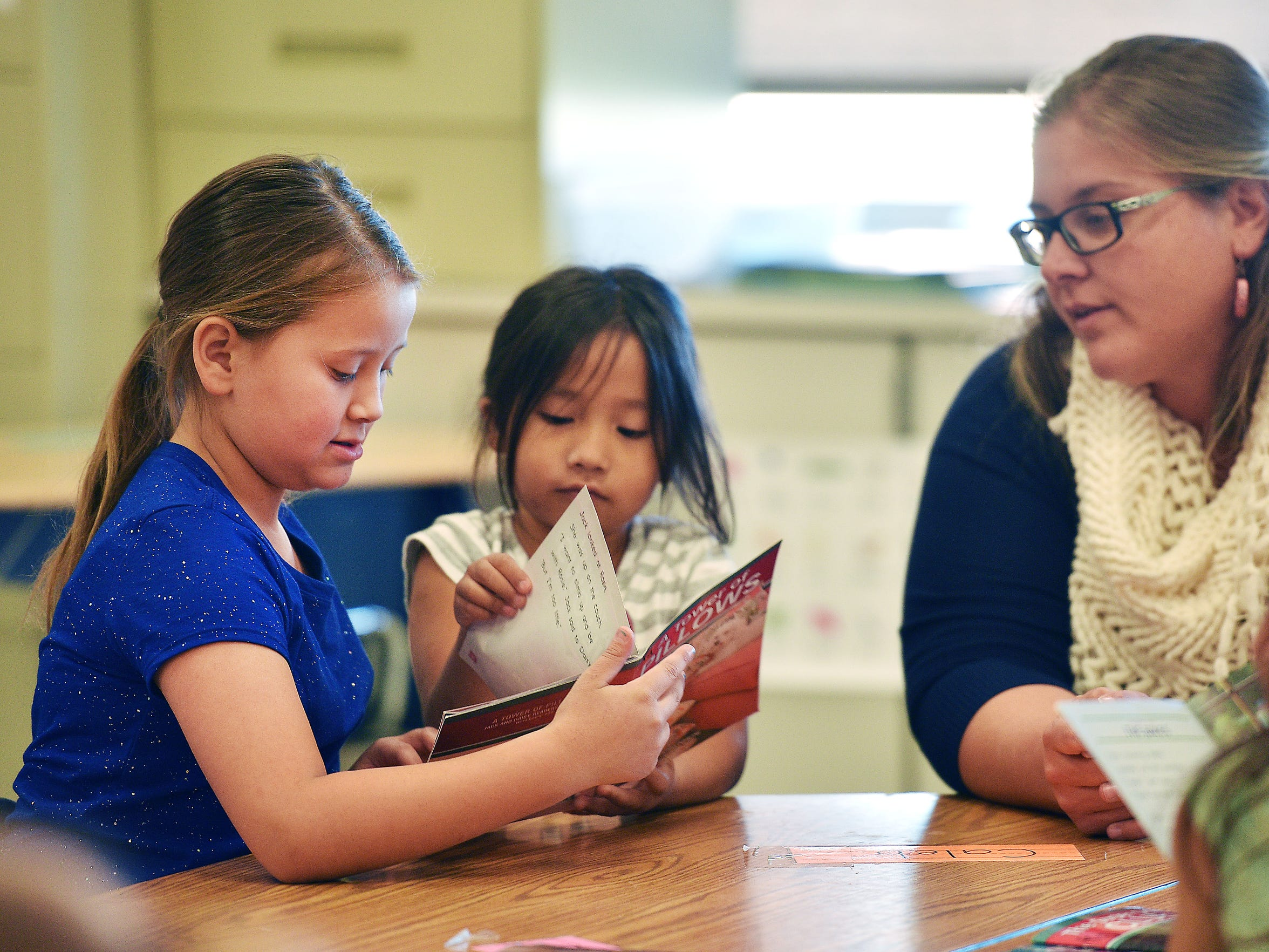 Third grader Aubrianna Haukaas, from left, reads a book to kindergartener Emily Songer and state paraprofessional educator Katie Sayler Wednesday, Nov. 15, at Todd County Elementary School in Todd County, South Dakota. Todd County Elementary School third grade students spend reading time with younger students at the school.